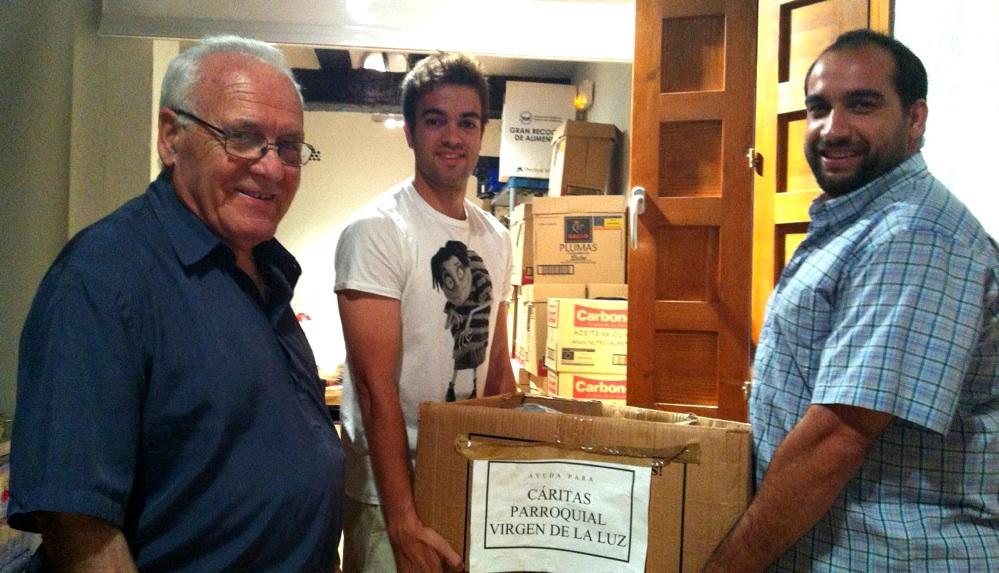 Los capitanes entregando la comida recogida para el banco de alimentos de la parroquia a D. Ángel.